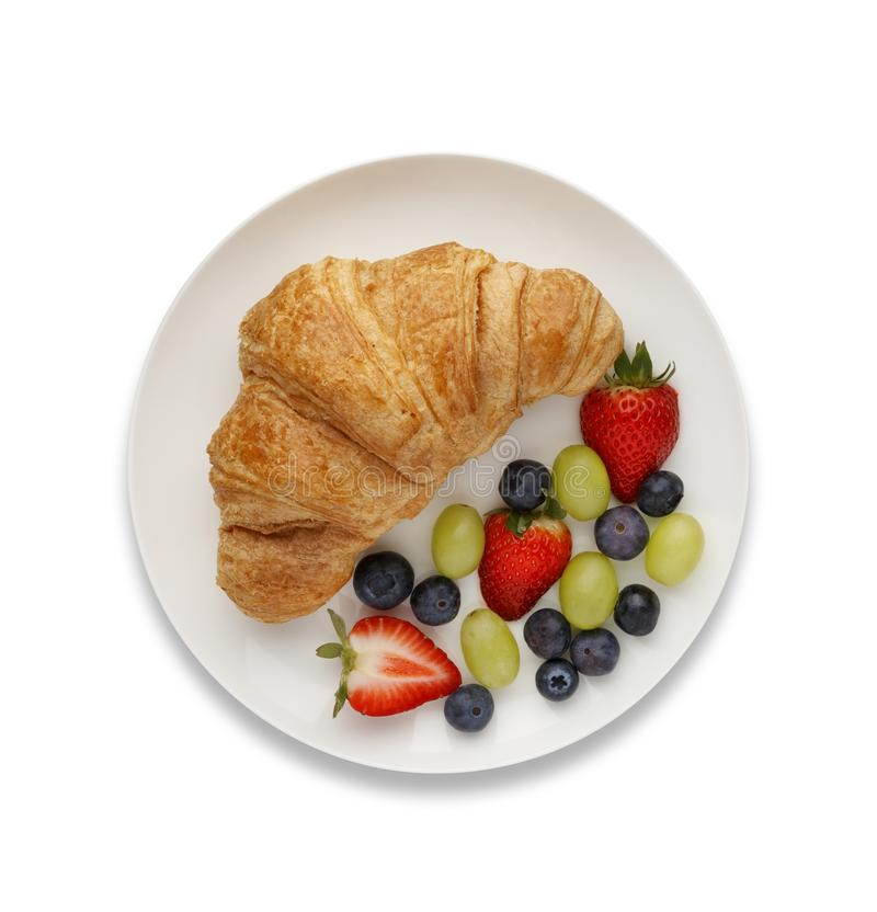 Continental breakfast of a croissant and fruit, shot from above, on white with a drop shadow. royalty free stock photography