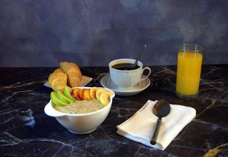 Continental breakfast, a cup of oatmeal with slices of fruit, orange juice, black coffee and two fresh croissants on a plate stock photos