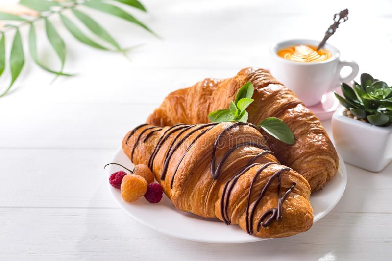Continental breakfast freshly baked croissant decorated with jam and chocolate on wooden table in a kitchen with copy royalty free stock photography