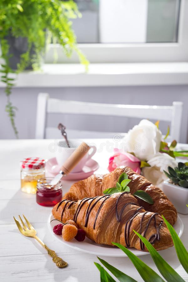 Continental breakfast freshly baked croissant decorated with jam and chocolate on wooden table in a kitchen with copy stock photos