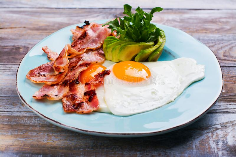 Continental breakfast with fried eggs, bacon and avokado royalty free stock images