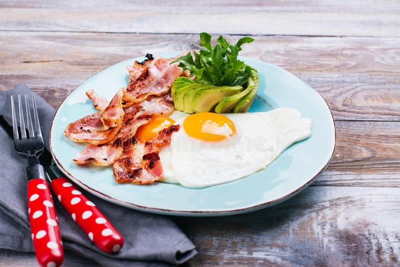 Continental breakfast with fried eggs, bacon and avokado. Continental breakfast with fried eggs, bacon and avocado. Ketogenic diet concept. Space for text stock photography