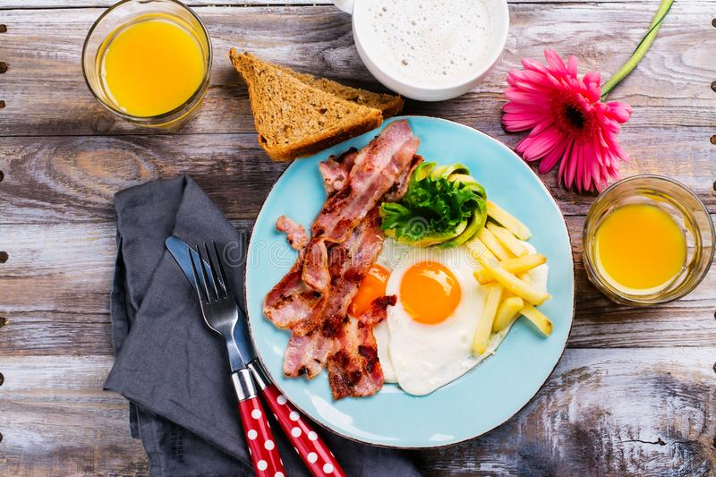 Continental breakfast with fried eggs, bacon and drinks. Ketogenic diet concept. Space for text stock photography