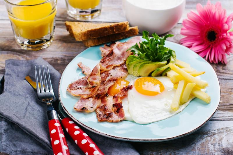Continental breakfast with fried eggs, bacon and drinks. Ketogenic diet concept. Space for text royalty free stock photography