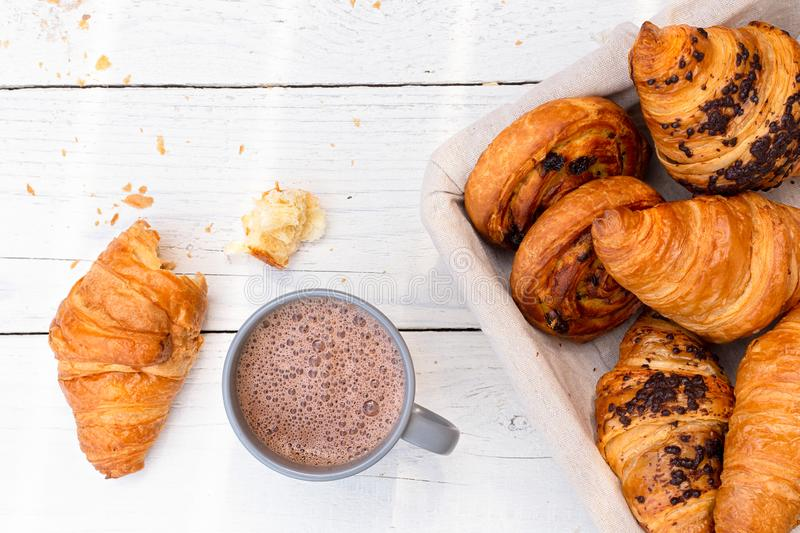 Continental breakfast with hot chocolate and basket of pastries. Half eaten on white wood from above.  royalty free stock photo