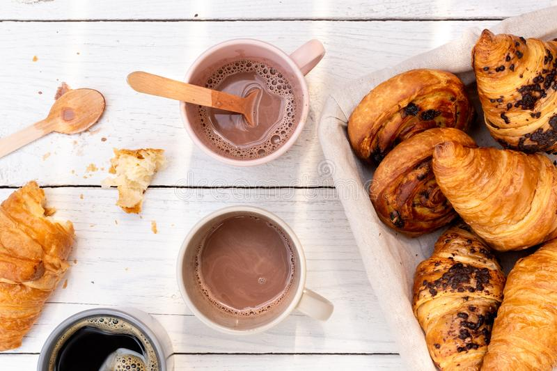 Continental breakfast with hot chocolate, black coffee and basket of pastries. Half eaten on white wood from above.  royalty free stock photo