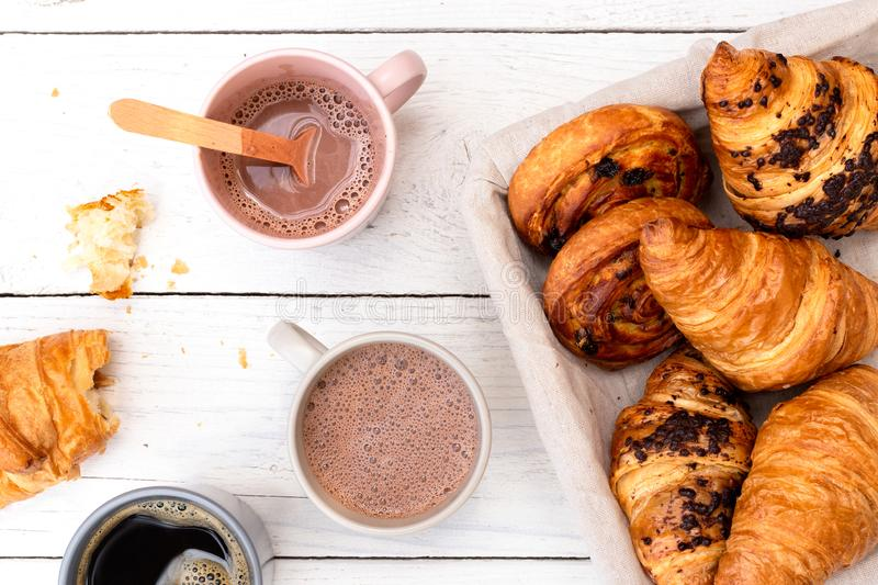 Continental breakfast with hot chocolate, black coffee and basket of pastries. Half eaten on white wood from above.  royalty free stock images