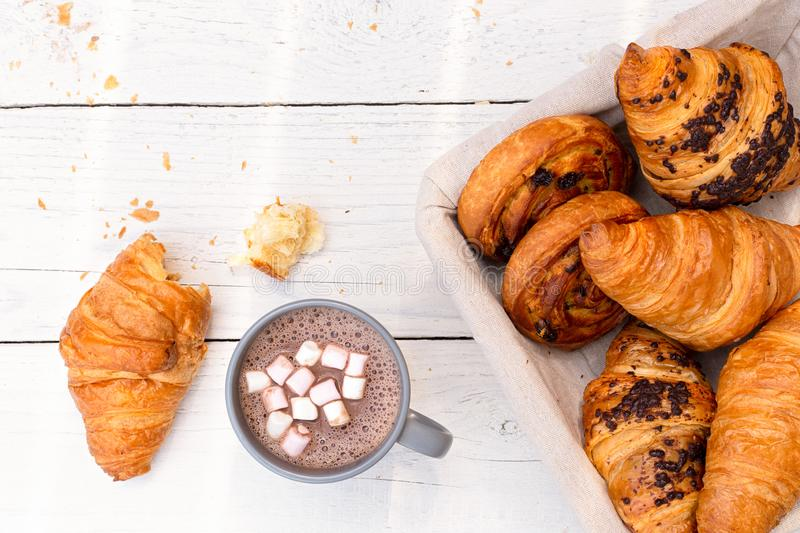 Continental breakfast with hot chocolate with marshmallows and basket of pastries. Half eaten on white wood from above.  stock image