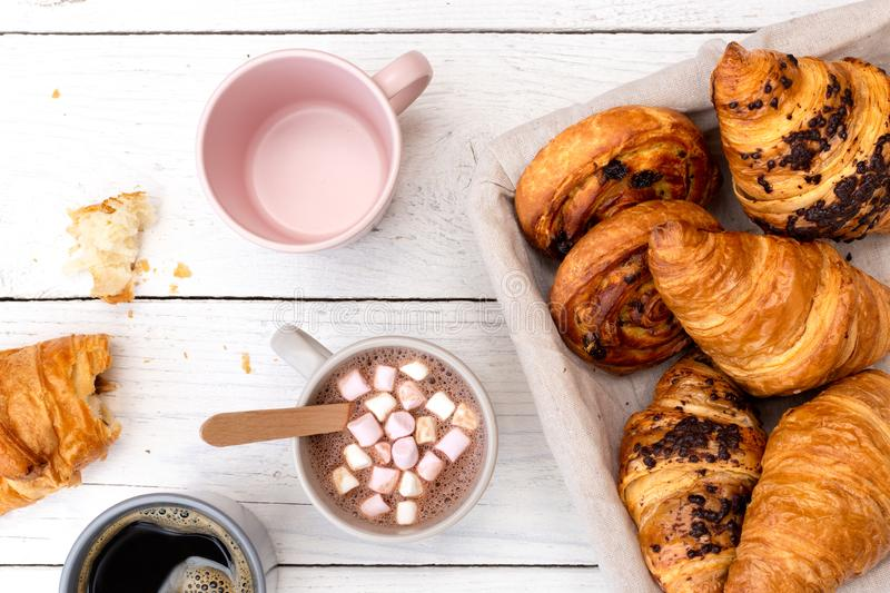 Continental breakfast with hot chocolate with marshmallows, black coffee and basket of pastries. Half eaten on white wood from. Above stock photo