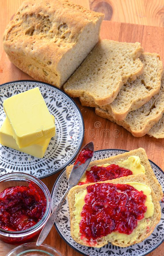 Continental breakfast -loaf of bread with butter and jam. Continental breakfast -loaf of bread with fresh butter and strawberry jam stock photo
