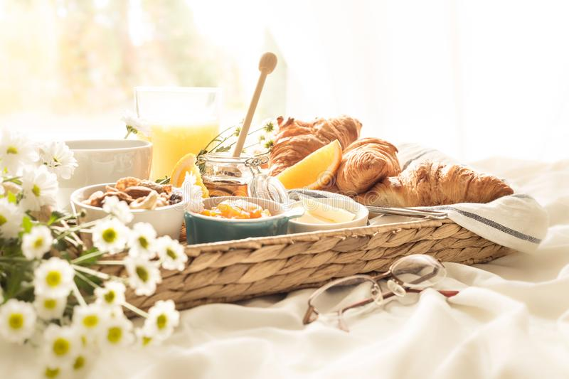 Wicker tray with continental breakfast on white bed sheets royalty free stock images