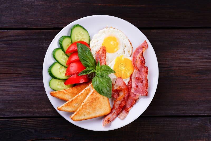 Continentale ontbijt Gebraden eieren met bacon, toosts en vers v stock foto's