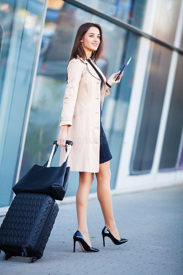 Continuação fêmea de sorriso do passageiro à porta de saída que puxa a mala de viagem através do ajuntamento do aeroporto imagem de stock royalty free
