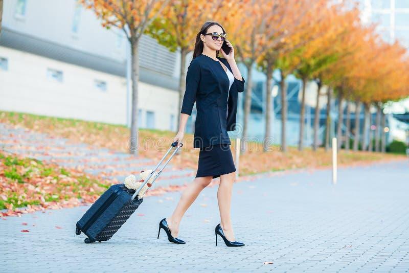 Continuação fêmea de sorriso do passageiro à porta de saída que puxa a mala de viagem através do ajuntamento do aeroporto imagens de stock