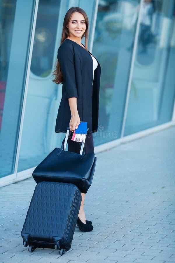 Continuação fêmea de sorriso do passageiro à porta de saída que puxa a mala de viagem através do ajuntamento do aeroporto fotos de stock royalty free