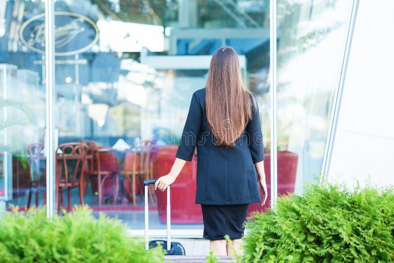 Continuação fêmea de sorriso do passageiro à porta de saída que puxa a mala de viagem através do ajuntamento do aeroporto imagem de stock