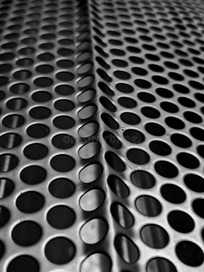 Continuation. Endleas endless holes monochrome blackandwhite macro metal stock image
