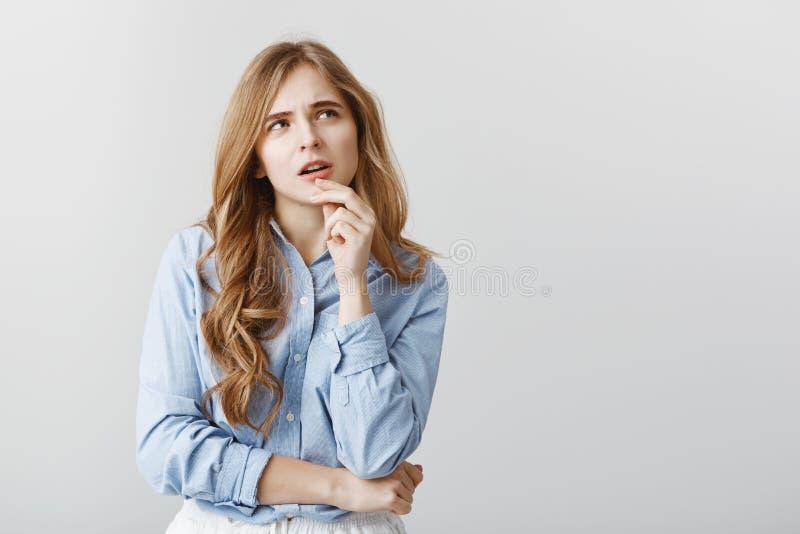 Continue bantar eller beställer pizza Stående av den ifrågasatte tänkande attraktiva kvinnan med blont hår och krullning, rörande royaltyfri fotografi