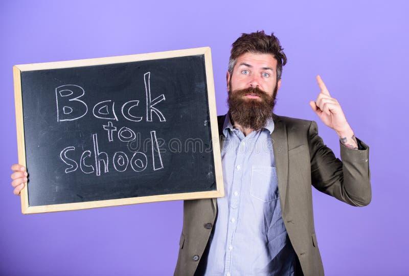 Continue sua educação connosco O homem farpado do professor está e guarda o quadro-negro com inscrição de volta à violeta da esco foto de stock royalty free