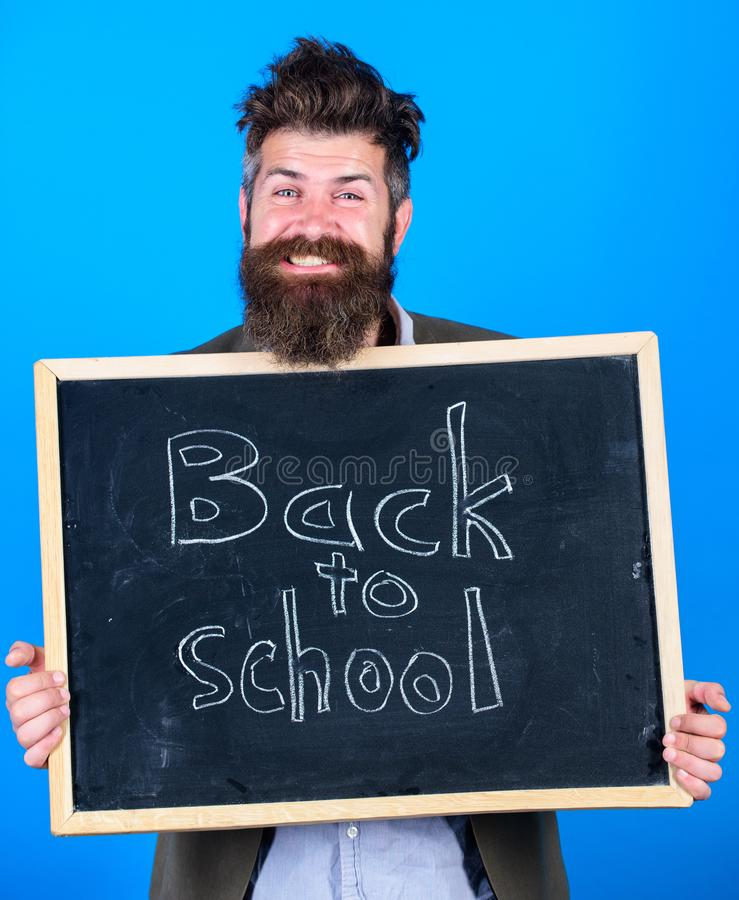 Continue sua educação connosco O homem farpado do professor está e guarda o quadro-negro com inscrição de volta ao azul da escola imagem de stock royalty free