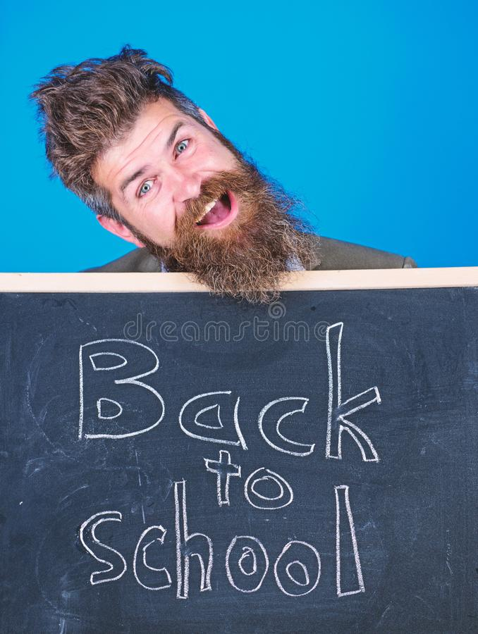 Continue your education with us. Teacher invites to continue studying. New semester in school. Teacher bearded man. Stands and holds blackboard with inscription stock photos