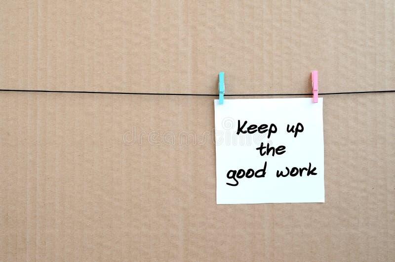Continui il buon lavoro La nota è scritta su un autoadesivo bianco che h fotografia stock