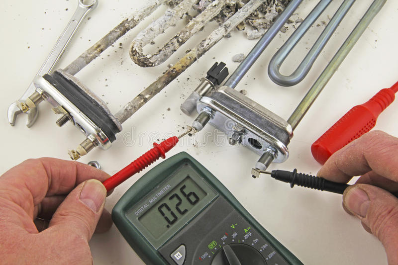 Continuity check. Appliance engineer using a multimeter carrying out a continuity test on a new heating element before installation stock images