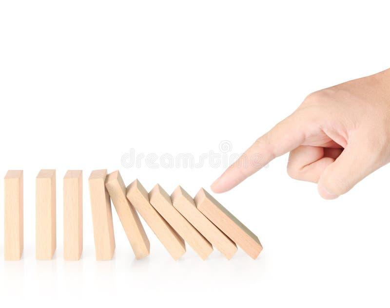 Continuo de los dominós de la parada de la mano derribado foto de archivo