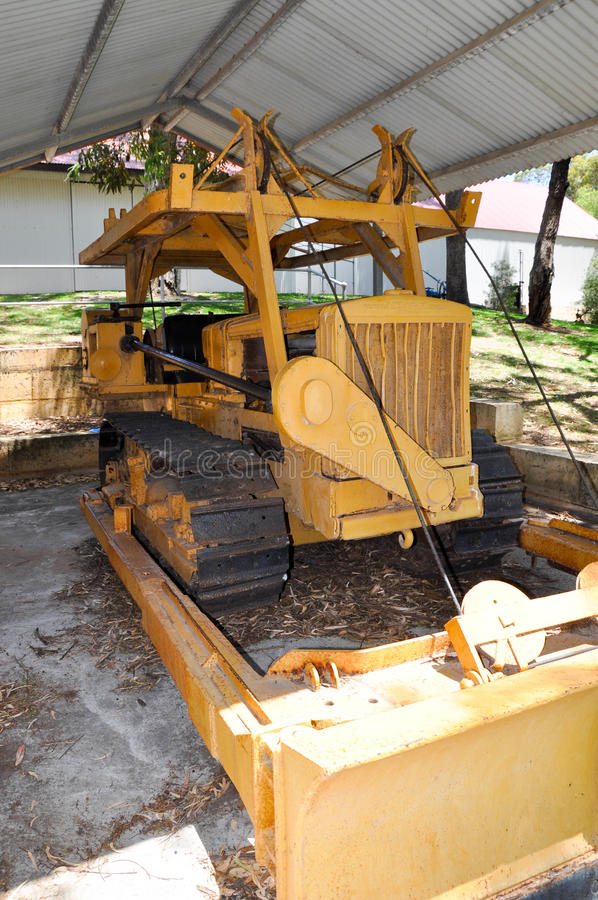 Continuous Track: Bulldozer Equipment. Continuous track bulldozer farm machinery in classic yellow under an outdoor shelter stock photo