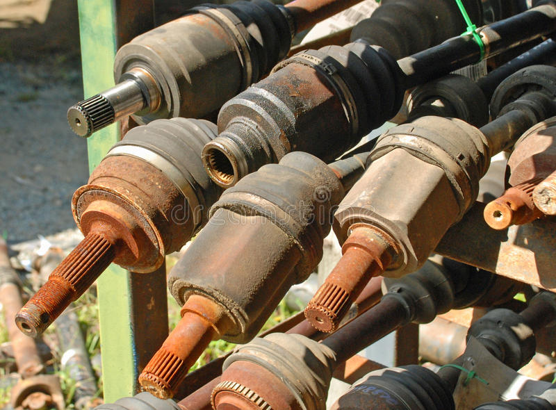 Continuous Velocity Axles At a Junkyard. Continuous Velocity Axles rest on racks at a junkyard. Some are rusted and greasy stock photography