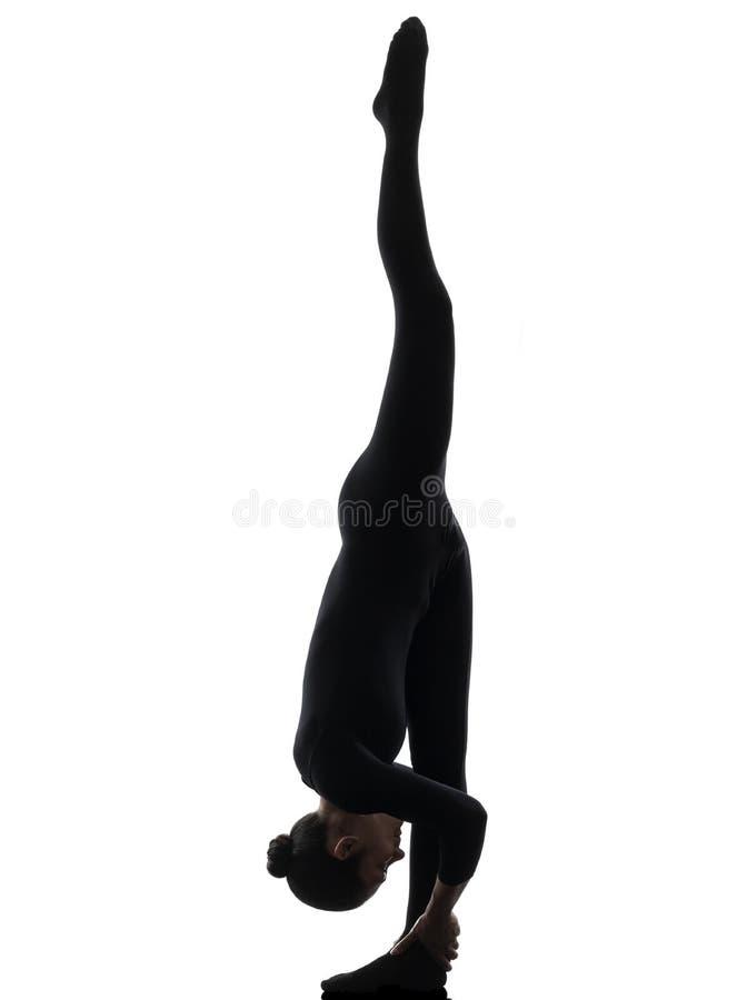 Contorcionista da mulher que exercita a ioga ginástica   silhueta imagens de stock