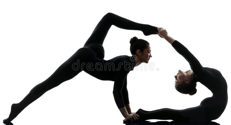 Contorcionista de duas mulheres que exercita a ioga ginástica