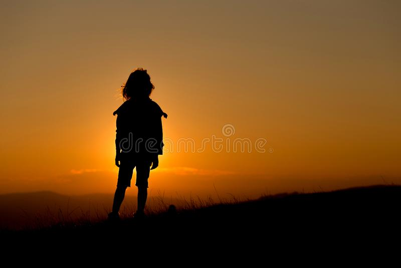 Contorni di un bambino che guarda il tramonto fotografia stock