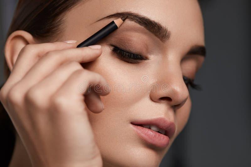 Contorno das sobrancelhas Mulher bonita com o lápis de sobrancelha de Brown imagem de stock
