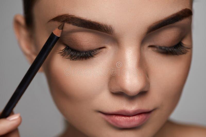 Contorno das sobrancelhas Mulher bonita com o lápis de sobrancelha de Brown fotografia de stock royalty free