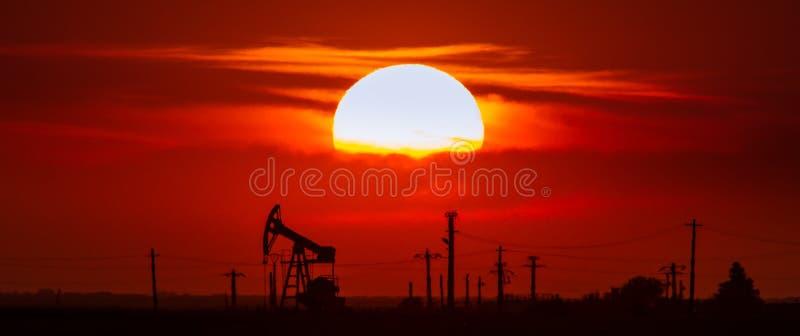 Contorno de funcionamento do poço de petróleo e gás, esboçado no por do sol fotografia de stock royalty free
