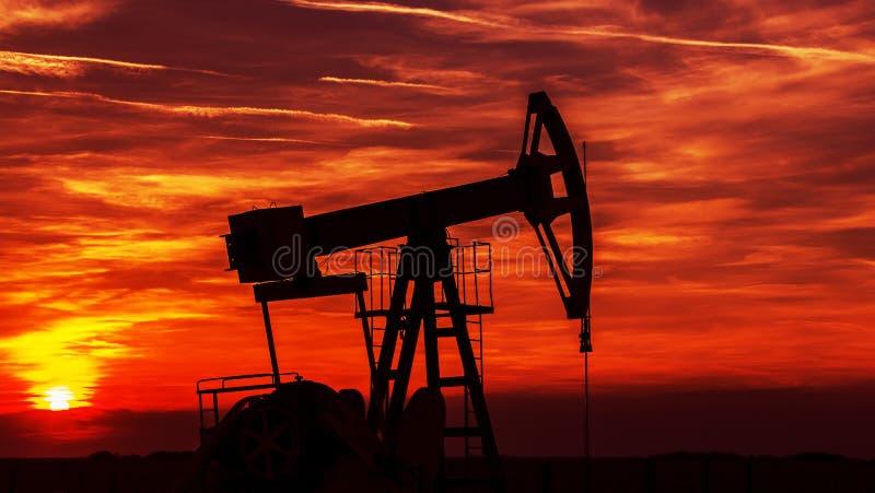Contorno de funcionamento do poço de petróleo e gás, esboçado no por do sol imagem de stock