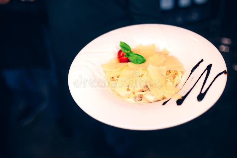 Contorno di insalata servente degli spaghetti della pasta del cameriere al ristorante, vicino sulla vista Concetto di svago e di  fotografia stock