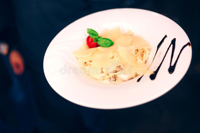 Contorno di insalata servente degli spaghetti della pasta del cameriere al ristorante, vicino sulla vista Concetto di svago e di  immagini stock libere da diritti