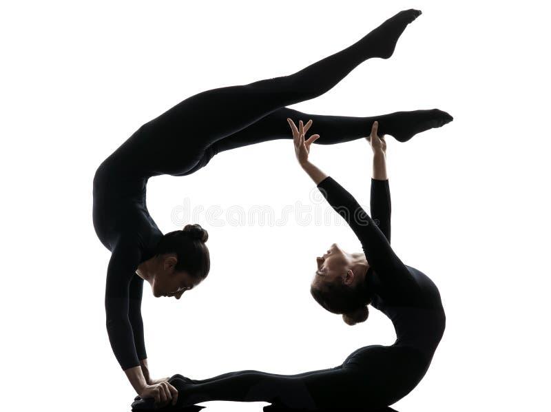 Contorsionist 2 женщин работая гимнастический силуэт йоги стоковое фото