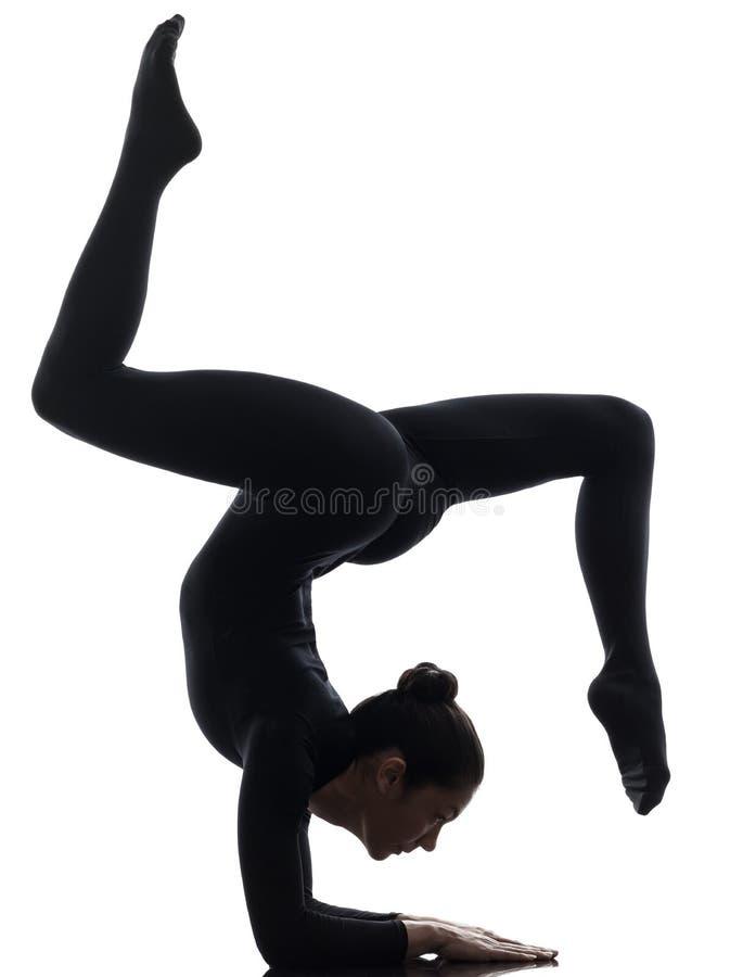 Contorsionist de la mujer que ejercita yoga gimnástica   silueta foto de archivo