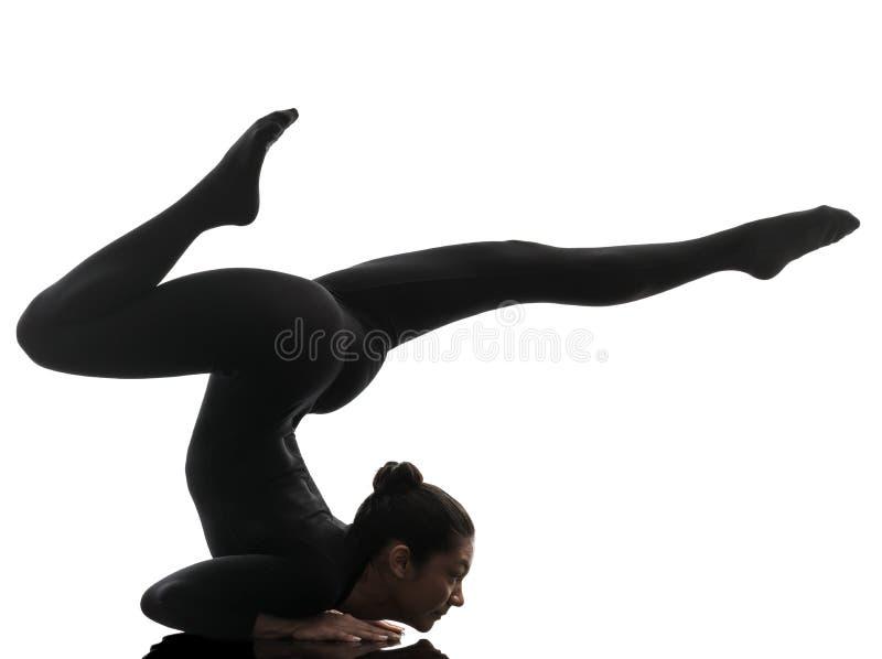 Contorsionista de la mujer que ejercita yoga gimnástica   silueta fotos de archivo libres de regalías