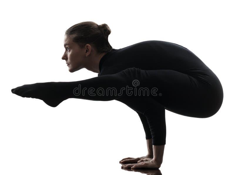 Contorsionista de la mujer que ejercita yoga gimnástica   silueta foto de archivo