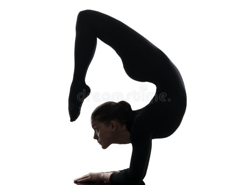 Contorsionista de la mujer que ejercita yoga gimnástica   silueta imagen de archivo