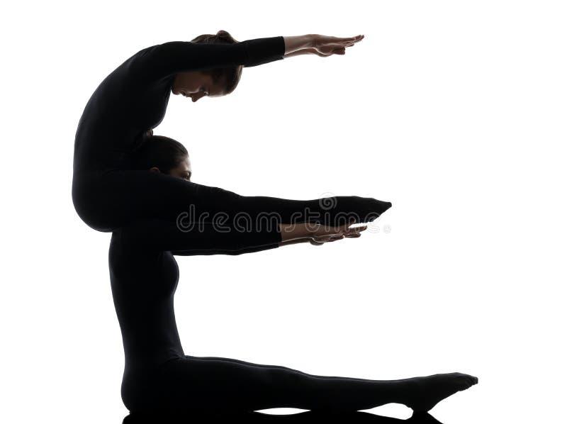 Contorsionniste de deux femmes exerçant la silhouette gymnastique de yoga photos stock