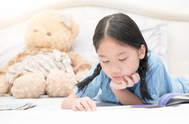 Contos de fadas asiáticos pequenos bonitos da leitura da menina na cama fotos de stock royalty free