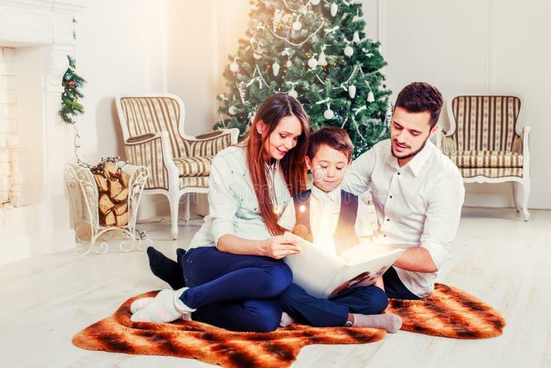 Contos de fadas felizes do Natal da leitura da família perto da árvore do Xmas Sala de visitas decorada pela árvore de Natal e pe fotos de stock royalty free