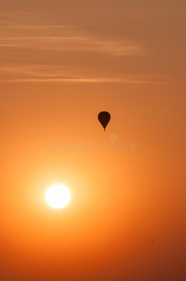 Balloon flying above the sun. Contour of balloon against the evening sky. Sunset in south-eastern Poland royalty free stock photography