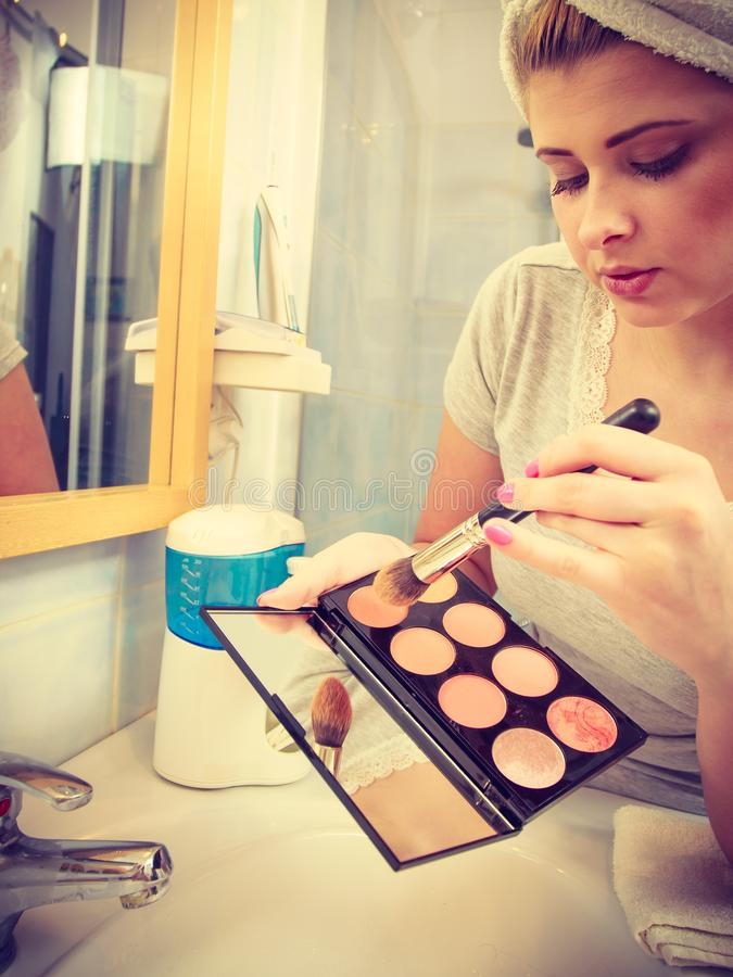 Woman in bathroom applying contour bronzer on brush. Contouring face kit, visage and make up concept. Woman in bathroom applying contour bronzer on brush stock image