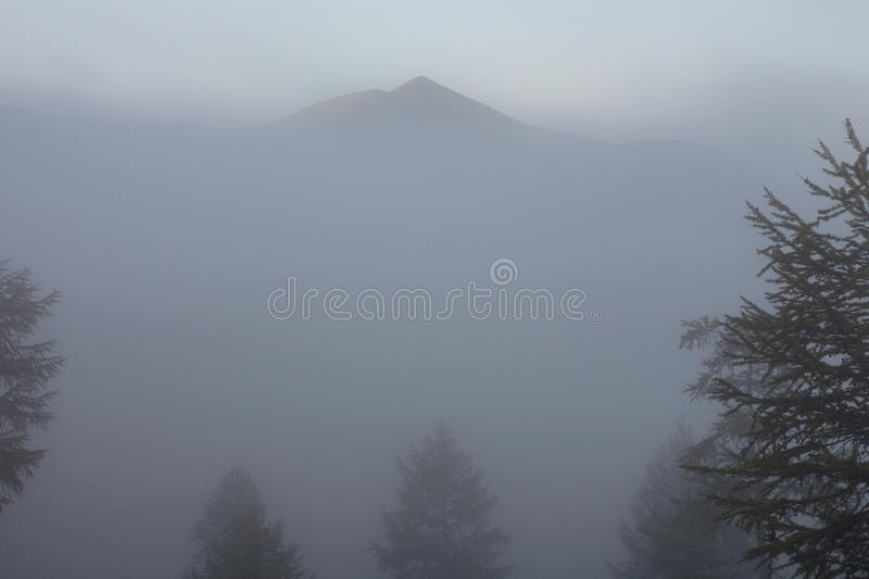 The contours of the mountain peaks and forests in the fog. Lake Labynkyr. Yakutia. Russia royalty free stock image